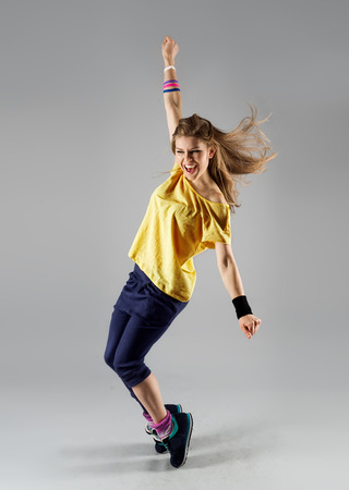 Energetic dancing woman screaming doing dance fitness exercise. Young beautiful jazz girl in motion.
