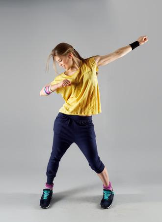 Modern actieve vrouwelijke kunstenaar dansen enthousiast poseren in de studio. Sport, gym en fitness. Stockfoto