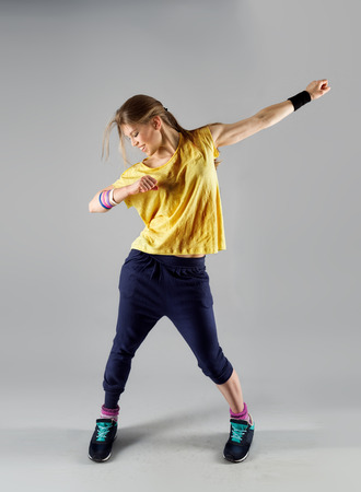 Modern active female artist dancing excited posing in studio. Sport, gym and fitness. Banque d'images