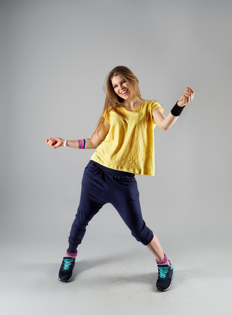 modern dance: Modern jazz dance workout. Portrait of happy smiling female doing sport in gym class.