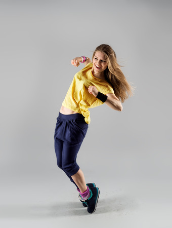 Excited dance fitness woman dancer training with fun over studio background. Sport and health concept.