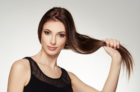 Schoonheid portret van jonge aantrekkelijke brunette haar gezonde glanzend haar te raken. Fashion blanke vrouw met lange rechte bruin haar poseren in de studio.