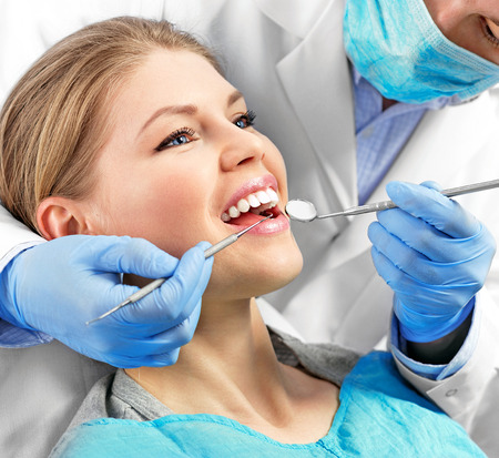 Dental health. Male dentist curing a female patient. 스톡 콘텐츠