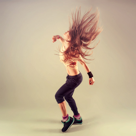 dance pose: Studio shoot of active female funk jazz dancer moving. Sport and leisure concept.
