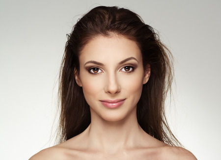 Portrait of attractive Caucasian female with wet hair looking at camera. Young lovely woman with professional makeup posing in studio.