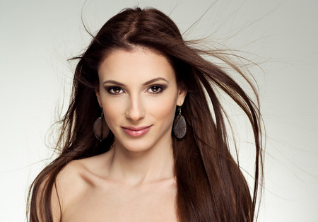 Close-up portrait d'attrayant modèle de salon femme de race blanche avec les cheveux au vent. Jolie jeune fille de la mode boucles d'oreilles pierreux posant en studio.