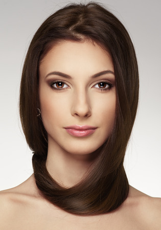 straight: Beautiful young woman with magnificent long hair looking at camera. Attractive Caucasian female model showing her glossy healthy hair.