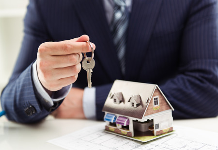 Male realtor selling house or apartment giving a key to client with building model at table. Shallow depth of field.