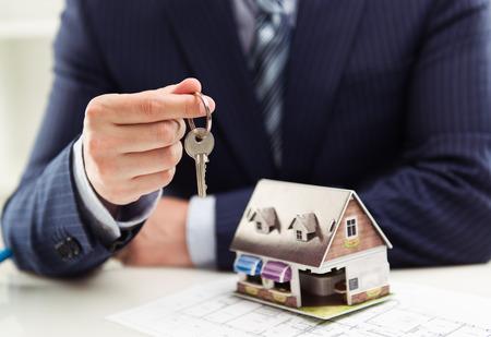Mannelijke makelaar in onroerend goed verkoop van huis of appartement met een sleutel tot klant met het bouwen van model aan tafel. Ondiepe scherptediepte. Stockfoto