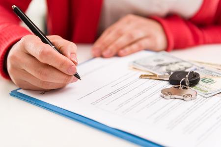Close-up van de vrouw de auto dealer ondertekenen huurcontract in het kantoor. Auto sleutel en geld op papieren. Ondiepe scherptediepte.