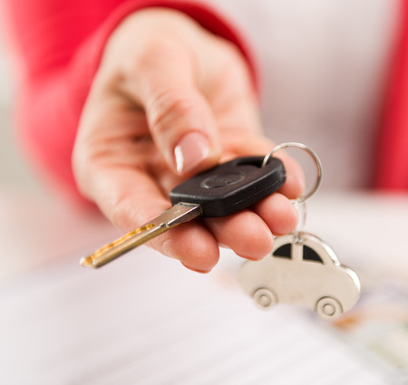 Closeup of female hand giving car key to buyer in automotive dealer Archivio Fotografico