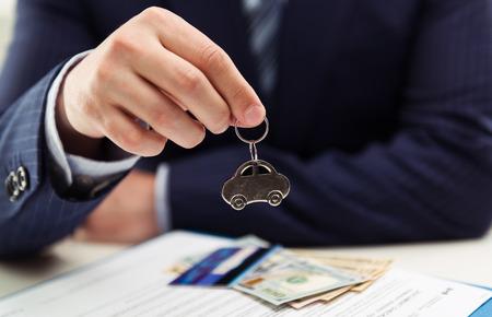 클라이언트에 자동차를 판매하는 남성 자동차 딜러. 임대, 투자 및 판매의 개념입니다. 필드의 얕은 깊이.
