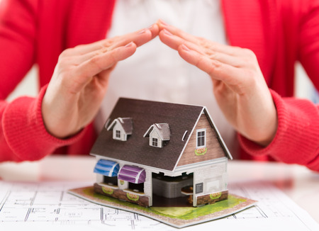Close-up of mortgage agent hands with family house model in real estate agency. Concept of real estate loan agreement. Shallow depth of field.