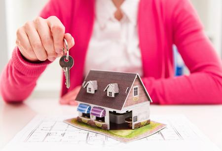 열쇠 고리를 들고 구매자 새 집 열쇠를 제공하는 부동산 중 손 확대 사진. 필드의 얕은 깊이. 스톡 콘텐츠