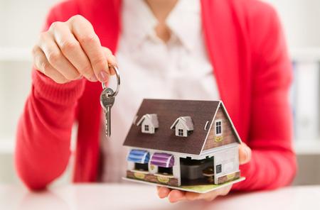 Close-up van vrouwelijke huis-agent houdt sleutelhanger van huurhuis. Onroerend goed contract. Ondiepe scherptediepte. Stockfoto