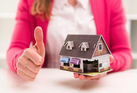 agente comercial: Mujer corredor de hipoteca que muestra el pulgar para arriba que se sienta en el escritorio en la oficina. Nueva casa de venta y alquiler. Foto de archivo