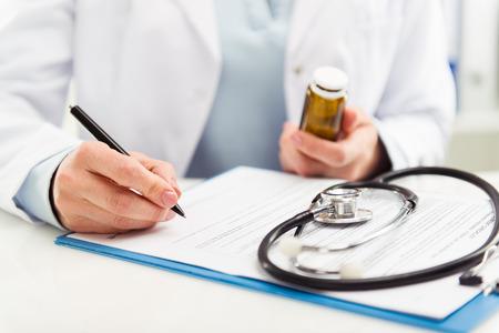 Médica, preenchendo o formulário médico na área de transferência, segurando a esferográfica e o frasco de medicamento. Conceito de saúde e seguro.