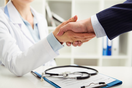 medical office: Woman doctor shaking hand with businessman in the office. Young medical specialist in uniform meeting partner for discussion. Shallow depth of field.