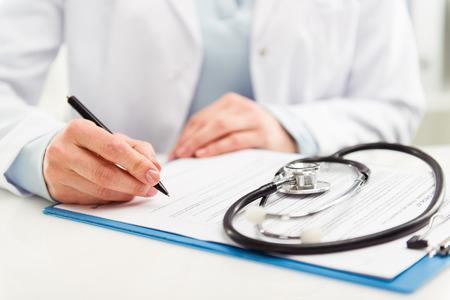 lekarz: Młoda kobieta z lekarzem stetoskop przepisywania leczenia do pacjenta. Kobieta lekarza z pióra do pisania receptury w schowku w szpitalu. Zdjęcie Seryjne