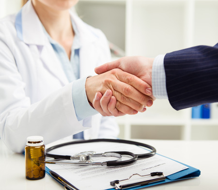 Woman doctor and businessman shaking hands in medical office. Concept of help, support and assistance. Shallow depth of field.