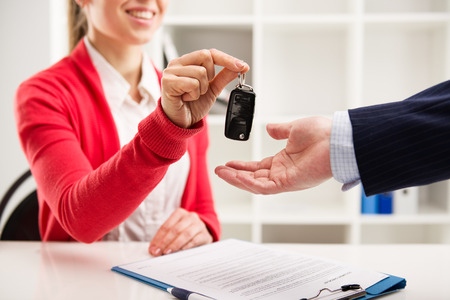 test drive: Female car agent giving key to male customer for test drive. Partnership and contract signing.