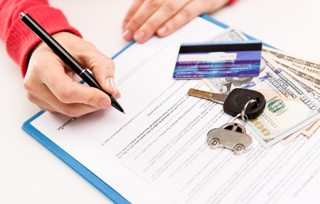 Young female leasing consultant signing car insurance contract Banque d'images