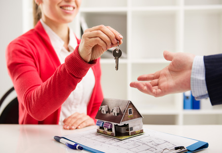 sell house: Closeup of smiling woman realtor giving key of new apartment to client. Female house agent sitting at the desk with house miniature and plan.