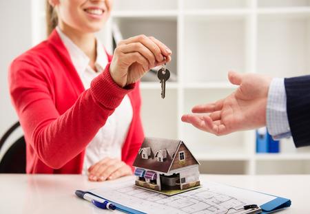 Primer de la mujer sonriente agente de bienes raíces que da clave de apartamento nuevo a cliente. Agente casa sentado en el escritorio con casa en miniatura y un plan. Foto de archivo