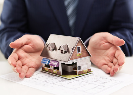 Male house agent showing family residence model to customers. Real estate agreement concept. Shallow depth of field.