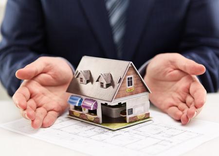 Mannelijke huisagent die het model van de familiewoonplaats aan klanten toont. Onroerend goed overeenkomst concept. Ondiepe scherptediepte. Stockfoto