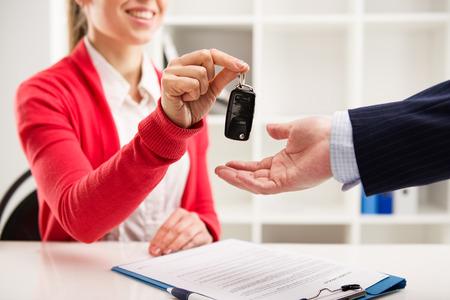 Vrouw auto-agent die sleutel geeft aan mannelijke klant voor proefrit. Partnerschap en ondertekening van het contract.