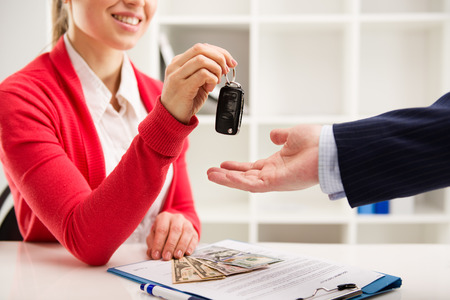 finance manager: Woman automotive dealer offering car key to buyer. Shallow depth of field.