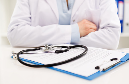 zdrowie: Bliska kobiet lekarza siedzi przy biurku z stetoskop i postaci medycznej. W leczeniu i opiece zdrowotnej. Płytkie głębi pola. Zdjęcie Seryjne