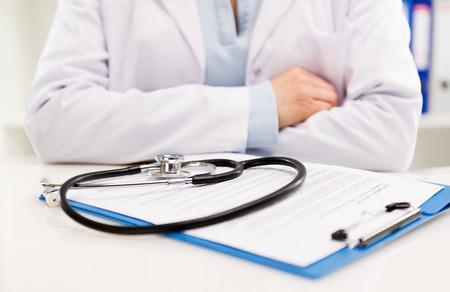 salute: Primo piano del medico femminile seduta alla sua scrivania con stetoscopio e certificato medico. Trattamento medico e assistenza sanitaria. Profondità di campo.