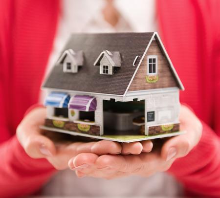 Close-up van de vrouw hypotheek adviseur houdt huis model. Concept van de nieuwe woning te koop of te huur. Ondiepe scherptediepte. Stockfoto