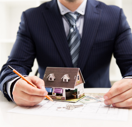 Young businessman working at house costing estimate and design. Male real estate agent sitting at the desk with blueprint, pencil and residence model.