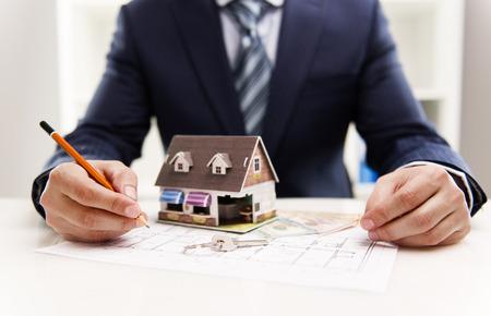 Gros plan d'hommes dessin d'architecte le plan de la maison à la clientèle du système de chauffage dans le bureau. Valeur de l'immobilier et le concept de coût. Faible profondeur de champ.