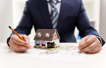ingresos: Primer plano de dibujo arquitecto plan de sistema de calefacción masculina de la casa del cliente en la oficina. Valor de las propiedades inmobiliarias y el concepto de costos. Poca profundidad de campo. Foto de archivo