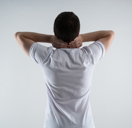 muscle strain: Young man having neck injury. Back muscle strain. Back massage and therapy concept.