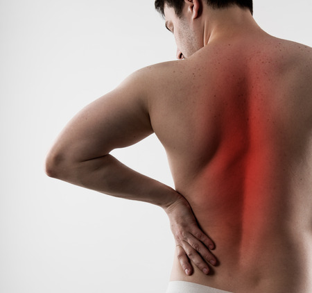 muscle spasm: Back inflammation and ache. Young man suffering from backbone disease or spasm. Stock Photo