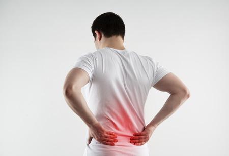 symptoms: Lumbago symptom. Young man holding his painful loin.