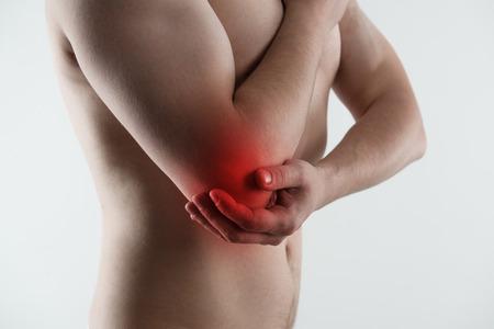 luxacion: Dolor Dolor de codo. Esguince y artritis síntomas. Varón joven tocando su brazo herido sobre fondo gris claro. Foto de archivo