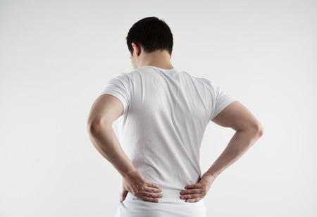 Caucasian man suffering from loin strain. Backbone treatment. Standard-Bild