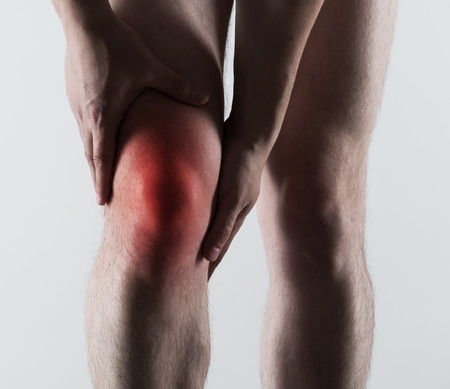 bone fracture: Acute pain of male leg shown with red spot. Bone fracture, emergency concept. Stock Photo