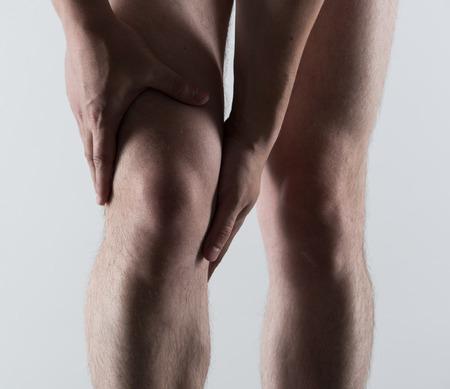 artrosis: Espasmo rodilla o lesiones. Hombre joven tocando su dolor de pierna. Foto de archivo
