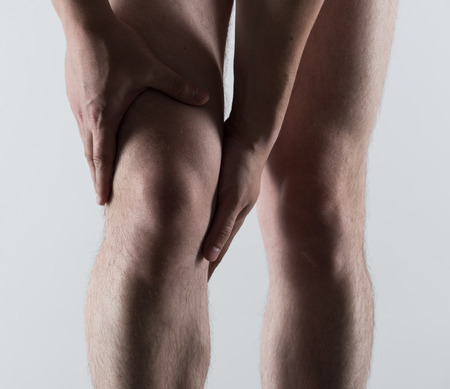 sore muscles: Knee spasm or injury. Young man touching his sore leg. Stock Photo