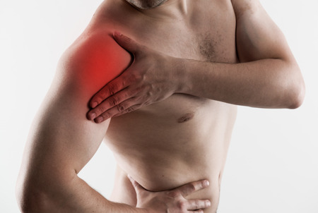 hand on shoulder: Shoulder joint fracture. Young man having rheumatism problem, touching his arm in pain. Stock Photo