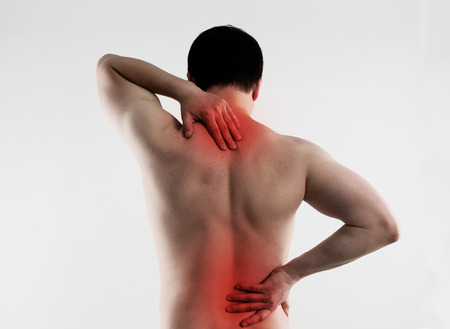 vertebrae: Backache on male body. Young person suffering from lumbar vertebrae disease. Stock Photo