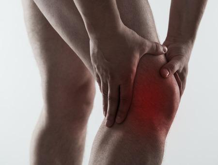 de rodillas: Mancha roja en la rodilla masculina dolorosa sobre fondo gris claro. Hombre que tiene el reumatismo y esguince problema. Foto de archivo