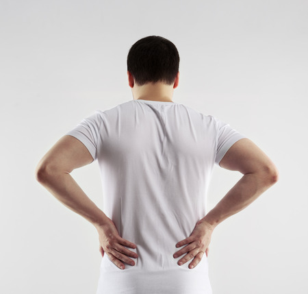 coccyx: Male painful back and loin. Young man touching his body in pain. Nerve spasm. Chronic ache concept.